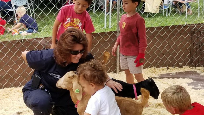 Deputy Fire Marshall Bower surrounded by goats and children